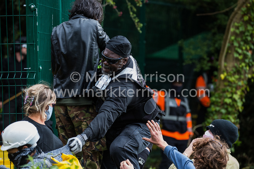 Denham, UK. 7th September, 2020. A National Eviction Team enforcement agent grasps the clothing of an HS2 Rebellion activist during direct action by anti-HS2 activists to prevent or delay tree cutting in conjunction with the high-speed rail link in Denham Country Park. Anti-HS2 activists continue to campaign and take direct action against the controversial £106bn project for which the construction phase was announced on 4th September from a series of protection camps based along the route of the line between London and Birmingham.