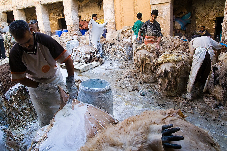 Workers at the Berber leather tannery in Fes El-Bali, Morocco, carve and clean the edges of sheep skins and coat them with lime on October 31, 2007. Chemical lime helps separate the wool from the leather.
