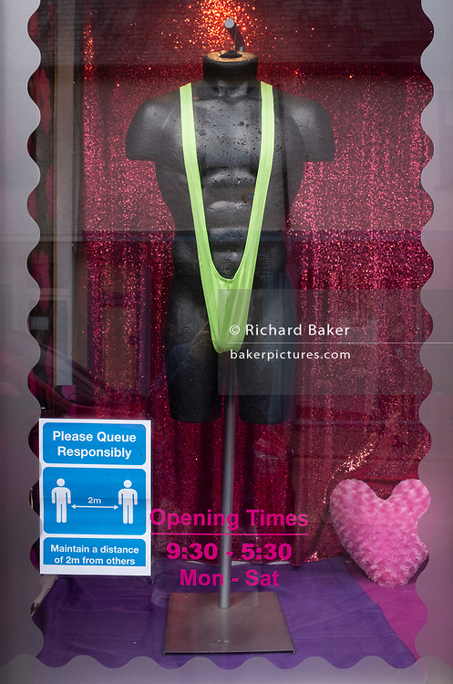 A detail of a window of an adult shop showing social distancing guidelines for responsible queueing customers during the Coronavirus pandemic lockdown, on 11th July 2020, in Bury St. Edmunds, Suffolk,