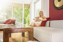 Beautiful young woman using digital tablet and sitting on sofa in the living room, Munich, Bavaria, Germany