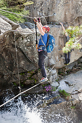 Woman climbing via ferrata towards Stuibenfall Waterfall, Otztal, Tyrol, Austria