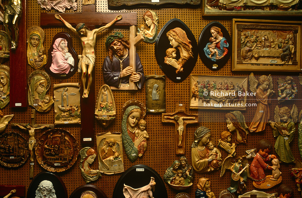 Christian religious icons, crucifixes, Last Supper depictions, virgin Marys and angels adorn a shop wall in central Lisbon.