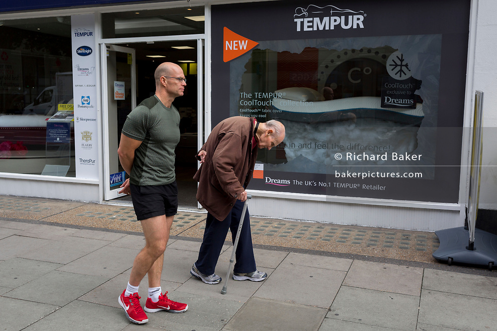 A very muscular, fit and upright man walks alongside a stooping elderly gentleman on Tottenham Court Road, on 3rd August 2017, in London, England.