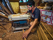 02 NOVEMBER 2016 - BANGKOK, THAILAND:  KO, Gob's brother, cuts teak for a spirit house. He works with his sister in the small family owned workshop that makes spirit houses by hand out of teak wood in the Ban Fuen community. There used to be 10 families making traditional spirit houses out of teak wood in Ban Fuen, a community near Wat Suttharam in the Khlong San district of Bangkok. The area has been gentrified and many of the spirit house makers have moved out, their traditional wooden Thai houses replaced by modern apartments. Now there is just one family making the elaborate spirit houses. The spirit houses are made by hand. It takes three days to make a small one and up to three weeks to make a large one. Prices start at about $90 (US) for a small one. The largest, most elaborate ones can cost over $1,000 (US). Almost every home and most commercial buildings in Thailand have a spirit house, which is a shrine to the protective spirit of a the land. Spirit houses are also common in Burma, Cambodia, and Laos.       PHOTO BY JACK KURTZ
