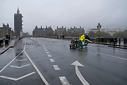 A workman drags works barriers across the road on Westminster Bridge on a wet, rainy day opposite the Palaces of Westminster, on 21st October 2020, in London, England.