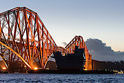 UB14, the Aft Island section of the second Queen Elizabeth Class aircraft carrier sails on a barge underneath the Forth Rail Bridge on it's way from Glasgow to the Rosyth Naval Dockyard, where it will be lifted on top of the rest of the sections that have been fitted together to complete the building of the ship.<br /> <br /> © John Linton<br /> All rights reserved