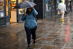 © Licensed to London News Pictures. 14/09/2021. London, UK. A woman shelters under an umbrella during heavy rain in Greenwich, South East London  . A yellow weather warning for rain is in place in parts of England . Photo credit: George Cracknell Wright/LNP