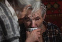 Valentina, 76, hjelps her husband, Nikolai, 77, take his medicine at their home in Debalseve. Nikola suffers from chronic cardia disease and is bed-ridden and relies on his wife to look after him.  MSF have recently begun a home visits project that sends teams of doctors and nurses into the community to deliver care to the hardest to reach patients.