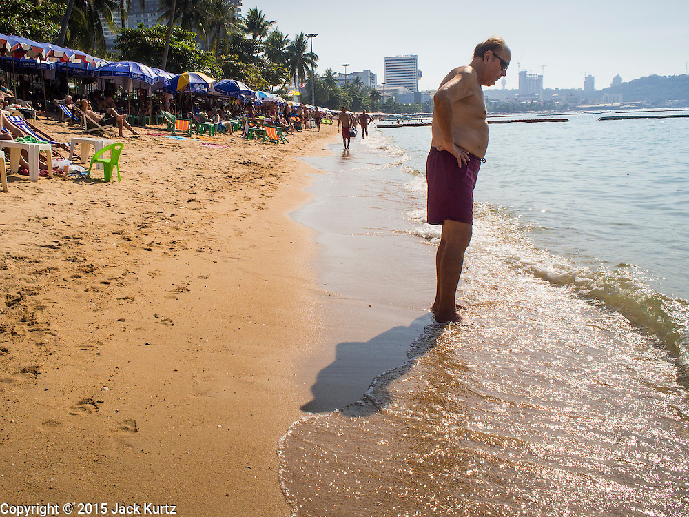 06 JANUARY 2015 - PATTAYA, CHONBURI, THAILAND:  A tourist walks along the water on Pattaya beach. The Thai government has announced plans to clean up Pattaya beach, one of the most famous beaches in Thailand. Pattaya is about 2.5 hours from Bangkok. They plan to reduce the number of umbrella and chaise lounge vendors on the beach and regulate the personal watercraft and parasailing vendors on the beach. The government has already cleaned up beaches on Phuket island and Hua Hin.   PHOTO BY JACK KURTZ