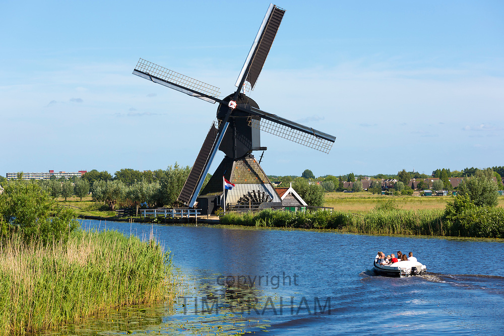 Tourists in boat pass authentic windmill at Kinderdijk UNESCO World Heritage Site, dykes and polder, Holland, The Netherlands