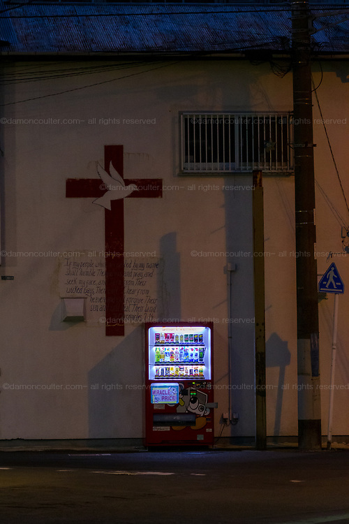 """YA vending machine showing a """"Miracle prices"""" signs in front of a church wall with a crucifix in Yamato, Kanagawa, Japan. Sunday January 5th 2020"""