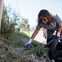 Francina Smith helping to clean up an alley in the Mossman neighborhood, Wednesday, Sept. 12, 2018. She and the rest of the clean-up crew are graduates of Rehoboth McKinley Christian Substance Abuse Treatment Center and are removing trees, shrubs and brush from the alleyways as a preventative measure to curb break-ins in the area.