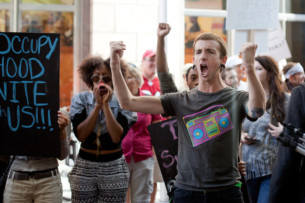 A young man attempts to arouse the crowd of protestors during a protest in front of Bank of America headquarters in uptown Charlotte, NC.