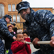 BATH, Maine --  US Navy Petty Officer 1st Class Reginald Glover helps out Kenneth and Royce Kirk, ages 5 and 4 respectively, wearing red, during the Blarney Days tug-o-war on Saturday. After Navy sailors stationed in Bath had a tug-o-war (between the Junior Enlisted and the Chiefs) they yielded the rope to the kids, who hauled with vigor as part of Blarney Days events in downtown Bath this weekend. Photo by Roger S. Duncan for The Forecaster.