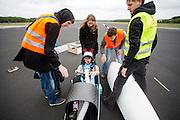De vrouwelijke rijder Christien Veelenturf wordt in de fiets geholpen. In Soesterberg test het Human Power Team Delft en Amsterdam (HPT) voor het eerst met de nieuwe fiets, de VeloX4. Op de voormalige vliegbasis legt de recordfiets de eerste meters af. In september wil het HPT, dat bestaat uit studenten van de TU Delft en de VU Amsterdam, een poging doen het wereldrecord snelfietsen te verbreken, dat nu op 133,8 km/h staat tijdens de World Human Powered Speed Challenge.<br /> <br /> In Soesterberg the Human Power Team Delft and Amsterdam (HPT) tests their newest bike, the VeloX4. On the track of the former military airport the bike rides its first meters. With the special recumbent bike the HPT, consisting of students of the TU Delft and the VU Amsterdam, also wants to set a new world record cycling in September at the World Human Powered Speed Challenge. The current speed record is 133,8 km/h.Nederland, Soesterberg, 08-05-2014