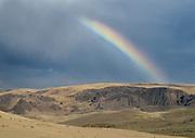 A rainbow falls from storm clounds onto the high desert of southeastern Oregon near Leslie Gulch