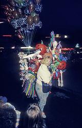 Female ballon vendor at parade. Stock photo
