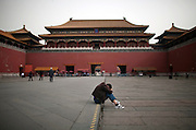 A man takes a rest in front of the main entrance of the Forbidden City in Beijing.