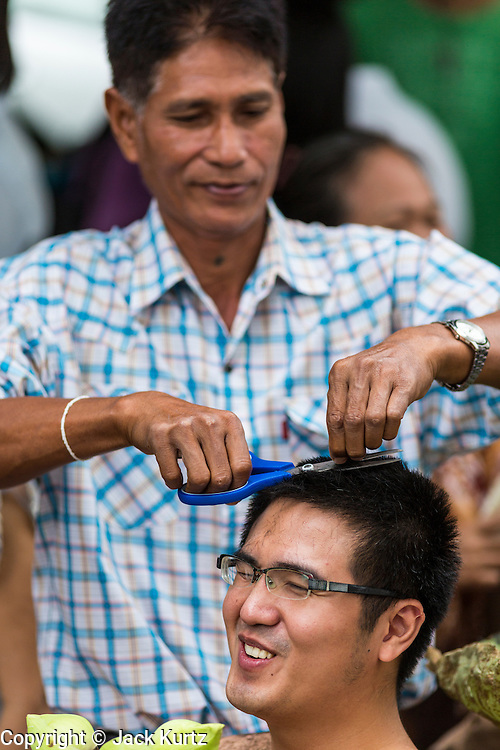 """21 JULY 2013 - BANGKOK, THAILAND:  A young man's family cuts his hair before he became ordained as a Buddhist monk at Wat Benchamabophit on the first day of Vassa, the three-month annual retreat observed by Theravada monks and nuns. Men frequently enter the monastery and become monks for Vassa. On the first day of Vassa (or Buddhist Lent) many Buddhists visit their temples to """"make merit."""" During Vassa, monks and nuns remain inside monasteries and temple grounds, devoting their time to intensive meditation and study. Laypeople support the monastic sangha by bringing food, candles and other offerings to temples. Laypeople also often observe Vassa by giving up something, such as smoking or eating meat. For this reason, westerners sometimes call Vassa the """"Buddhist Lent.""""       PHOTO BY JACK KURTZ"""