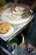 Ram Billas's foot resting on a tin whilst making paratha at Parawthe Wala restaurant in Old Delhi, India<br /> The parantha is an Indian fried bread, folded and filled with fillings and then fried.<br /> Gali Paranthe Wali or Paranthe wali Gali means the the street of fried bread and name of a narrow street in Chandni Chowk Old Delhi, noted for its series of shops selling paratha