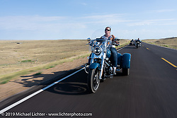 Jayne Zaleski rides her Tri-Glide in the Harley Owners Group (HOG) ride out from the Full Throttle Saloon during the Sturgis Motorcycle Rally. SD, USA. Thursday, August 12, 2021. Photography ©2021 Michael Lichter.