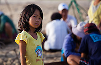 Young girl on the beach while the days catch are being sorted.