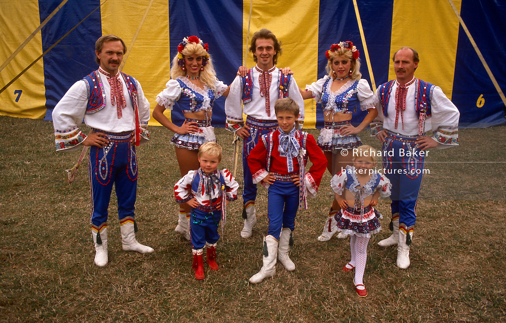 A circus family poses for a portrait outside their big top tent before performing at another local show in south London. The family members are from the well-known Czech Faltiny Troupe who are travelling here on a European tour with Gerry Cottle's Circus in 1990. Wearing traditional the costumes of east European performers, the adults and their children look happy with their lives in the circus ring.
