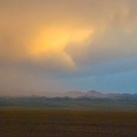 Sunset lights a rain squall over the Gobi Desert near Dalanzadgad, Mongolia.