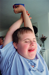 Portrait of teenage boy with Downs Syndrome stretching,