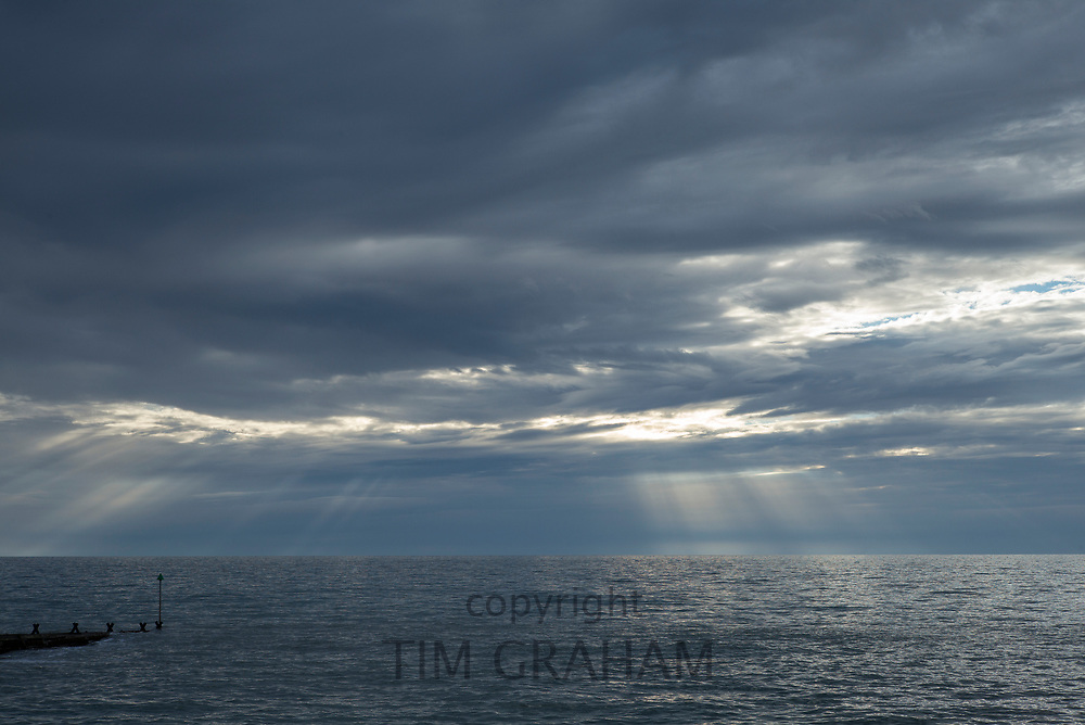 Rays of the sun breaking through dark cloud above the Atlantic Ocean at sunset in Wales