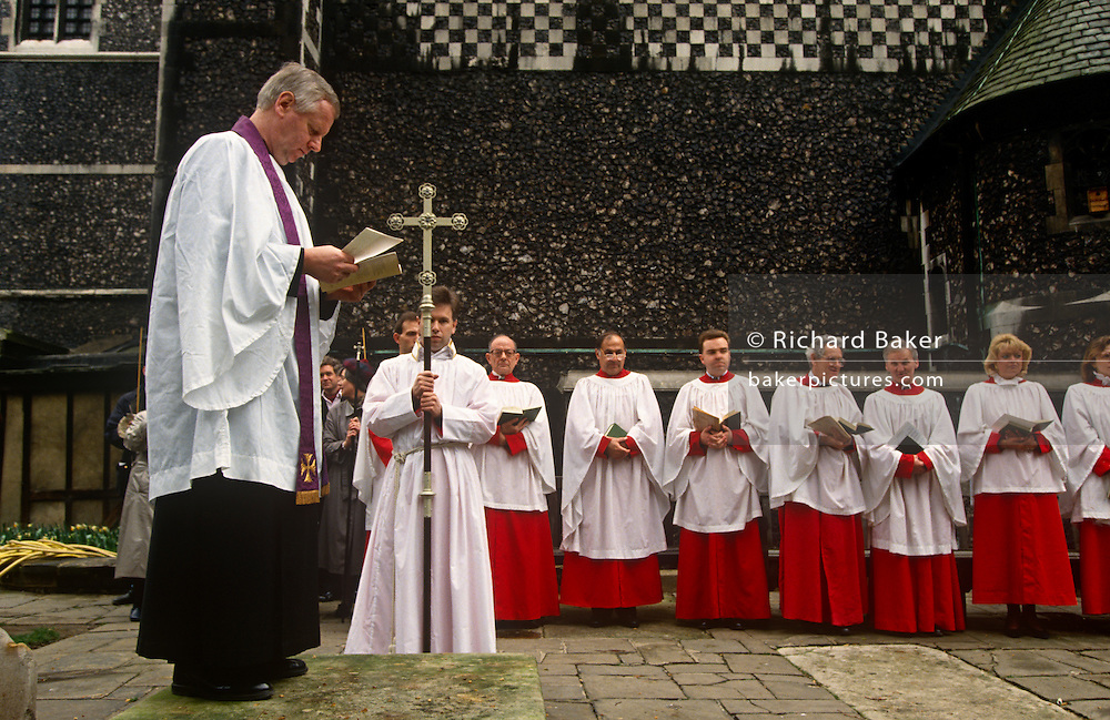 As an Anglican vicar leads an outdoors service, his choristers await the next hymn outside the Norman-built St Bartholomew the Great church in Smithfield, City of London. The Priory Church of St Bartholomew-the-Great is an Anglican church located at West Smithfield in the City of London, founded as an Augustinian priory in 1123.