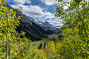 View up West Maroon Creek Valley, seen from Maroon-Snowmass Trail #1975 on descent from Buckskin Pass (11 miles round trip gaining 3000 feet) in Maroon Bells-Snowmass Wilderness of White River National Forest, near Aspen, Colorado, USA.