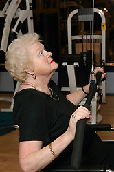 Woman wheelchair user using weights at an inclusive fitness gym,