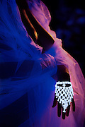 Bare chested woman with glowing white bracelet and veil.Black light
