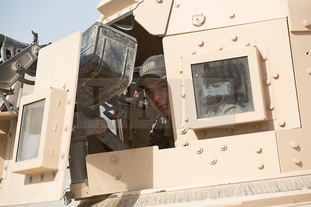 Licensed to London News Pictures. 11/11/2016. Mosul, Iraq. A soldier, belonging to the Iraqi Army's 9th Armoured Division, peers from the turret of an armoured Humvee as his unit visits Mosul's Al Inisar district on the south east of the city. The Al Intisar district was taken four days ago by Iraqi Security Forces (ISF) and, despite its proximity to ongoing fighting between ISF and ISIS militants, many residents still live in the settlement without regular power and water and with dwindling food supplies.<br /> <br /> The battle to retake Mosul, which fell June 2014, started on the 16th of October 2016 with Iraqi Security Forces eventually reaching the city on the 1st of November. Since then elements of the Iraq Army and Police have succeeded in pushing into the city and retaking several neighbourhoods allowing civilians living there to be evacuated - though many more remain trapped within Mosul.  Photo credit: Matt Cetti-Roberts/LNP