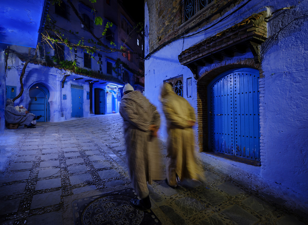 CHEFCHAOUEN, MOROCCO - CIRCA MAY 2018:  Two people walking in the main street of Chefchaouen at night.