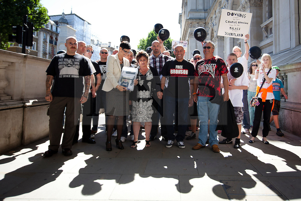 """© Licensed to London News Pictures. 31/08/2013. London, UK. Lorraine Etherington (front 2L), Lorraine Salvage (front 3L) and Mark Peterson (front 4L), sister, cousin and brother of of prisoner Charles Bronson, are seen with other friends and relatives before handing in a petition for his release to Number 10 Downing Street in London today (31/08/2013). Often referred to in the British press as the """"most violent prisoner in Britain"""", Bronson is currently being held on a life sentence in Wakefield High-Security Prison. Photo credit: Matt Cetti-Roberts/LNP"""