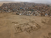 In this Oct. 5, 2017 photo, homes in the Lurin district encroach upon the pre-Columbian archeological site Pachacamac, in Lima, Peru. Many people in modern-day Peru recall treasure hunting in the ruins as children, hiding away pieces of ceramic pots, textile scraps and even human bones, remnants of the vast Inca empire that flourished more than six centuries ago.