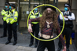 London, UK. 4th September, 2020. An activist from HS2 Rebellion, an umbrella campaign group comprising longstanding campaigners against the HS2 high-speed rail link as well as Extinction Rebellion activists, uses a hula hoop during a protest outside the Department for Transport. Activists glued themselves to the doors and pavement outside the building and sprayed fake blood around the entrance during a protest which coincided with an announcement by HS2 Ltd that construction of the controversial £106bn high-speed rail link will now commence.