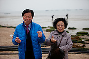 """Korean couple with mussels during low tide at Hoedong shore (Jindo Island). Jindo is the 3rd biggest island in South Korea located in the South-West end of the country and famous for the """"Mysterious Sea Route"""" or """"Moses Miracle"""" which is happening during full moon in spring."""