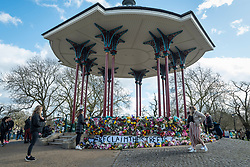 © Licensed to London News Pictures. 13/03/2021. LONDON, UK.  London, UK.  13 March 2021.  People lay floral tributes at the bandstand on Clapham Common to remember Sarah Everard.  Wayne Couzens, 48, a serving Met Police officer, has been charged with her kidnap and murder after she walked home in south London.  The 33-year-old's body was found in woodland in Kent more than a week after she was last spotted on 3 March.  Photo credit: Stephen Chung/LNP