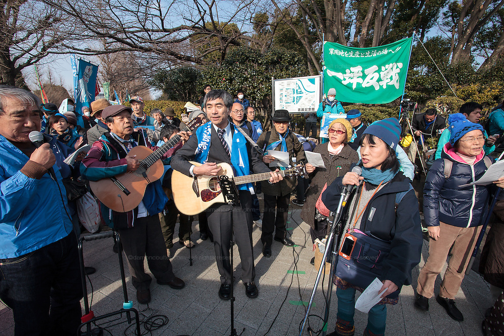 Protestors play guitars and sing at a rally to protest the construction of a new US military base at Henoko in Okinawa outside the Japanese National Diet building, Nagatacho, Tokyo, Japan Sunday January 25th 2015. Organisers say 7,000 people joined the protest which formed a human chain around the National Diet building