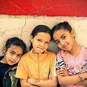 Three girls from Qarafa in Cairo pose in front of the wall they painted with Egypt's colours after their country's revolution.