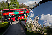 St. Pauls Cathedral and a London bus reflected in polished street art, the capitals financial district, on 19th April, in the City of London, England.