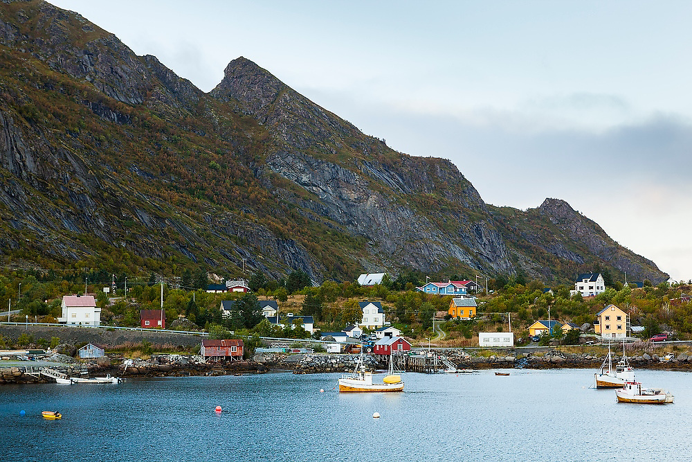 Small wooden boats and homes on the harbor in Moskenes, Lofoten Islands, Norway.
