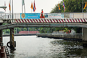 14 NOVEMBER 2012 - BANGKOK, THAILAND: A Buddhist monk walks on a bridge over the Khlong Saen Saeb at the Wat Sriboonreung Pier, the southern terminal of the Khlong Saen Saeb boat service. Bangkok used to be criss crossed by canals (called Khlongs in Thai) but most have been filled in and paved over. Khlong Saen Saeb is one of the few remaining khlongs in Bangkok with regular passenger boat service. Boats and ships play an important in daily life in Bangkok. Thousands of people commute to work daily on the Chao Phraya Express Boats and fast boats that ply Khlong Saen Saeb. Boats are used to haul commodities through the city to deep water ports for export.      PHOTO BY JACK KURTZ