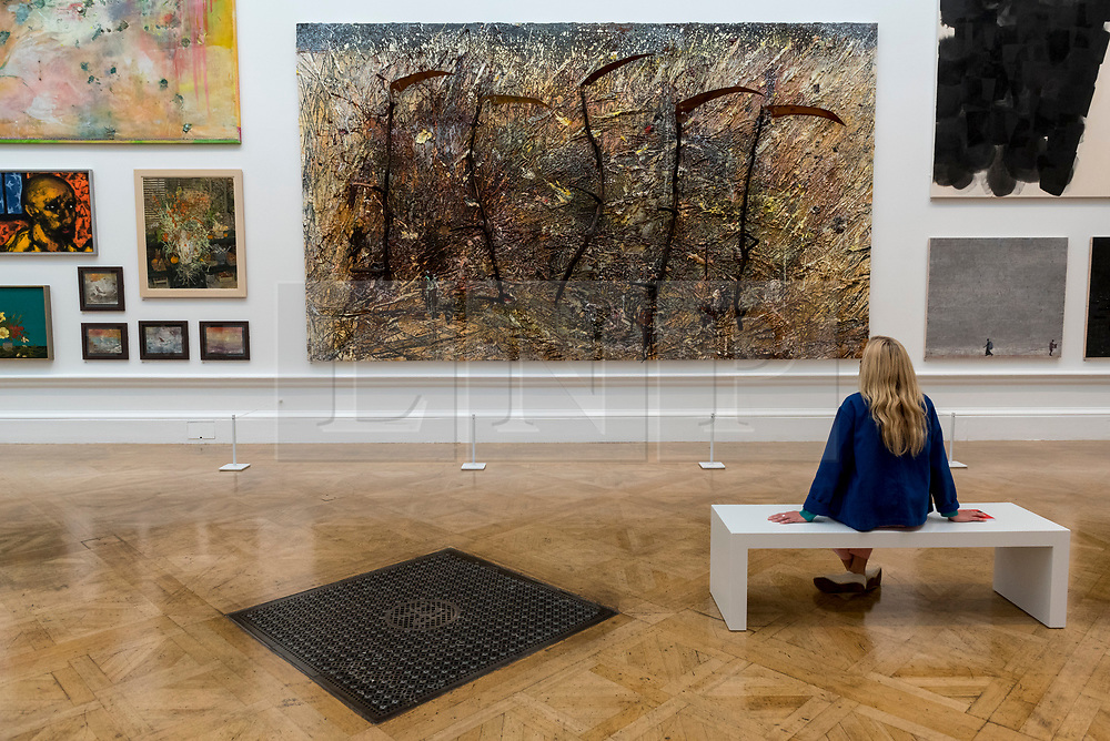 "© Licensed to London News Pictures. 28/09/2020. LONDON, UK. A staff member views with ""Vier Plus Eins"" by Anselm Kiefer (Hon RA).  Preview of the Summer Exhibition at the Royal Academy of Arts in Piccadilly which, due to the Covid-19 lockdown, is taking place for the first time in the autumn.  Over 1000 works in a range of media by Royal Academicians, established and emerging artists, feature in the exhibition which runs from 6 October 2020 – 3 January 2021.  Photo credit: Stephen Chung/LNP"