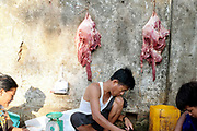 A butcher preparing meat at a market on the platform at Thamine station, one of the 39 stations of Yangon Circular Railway on 17th May 2016 in Yangon, Myanmar. The railway, a narrow gauge local commuter trail network serving Yangon metropolitan area is a 28.5 mile 45.9 km 39 station loop system. This British built rail-loop connects Yangon to its satellite towns and villages