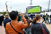 Tourist photographing the crowd watching the 2008 Rugby League Grand Final on a big screen set up outside Olympic Stadium. Sydney, Australia