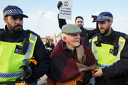 London, UK. 17th November, 2018. Police officers arrest Phil Kingston, 82, after he and other environmental campaigners from Extinction Rebellion blocked Blackfriars Bridge, one of five bridges blocked in central London, as part of a Rebellion Day event to highlight 'criminal inaction in the face of climate change catastrophe and ecological collapse' by the UK Government as part of a programme of civil disobedience during which scores of campaigners have been arrested.